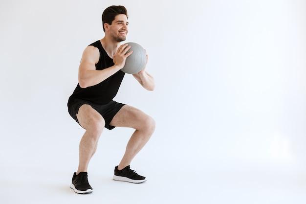 Poważny silny młody sportowiec zrobić przysiady ćwiczenia z piłką na białym tle.