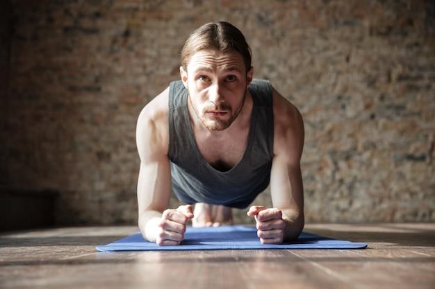 Poważny silny sportowiec na siłowni wykonuje ćwiczenia jogi.
