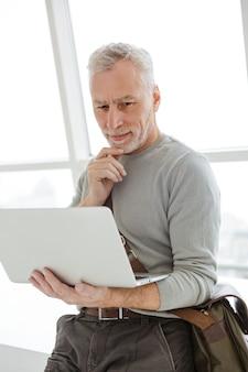 Poważny siwowłosy mężczyzna trzymający laptopa i używający go, stojąc w pobliżu okien w pomieszczeniu