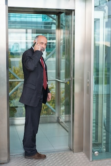 Poważny skoncentrowany dojrzały właściciel biznesu rozmawia przez komórkę
