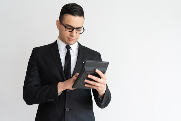 Poważny skoncentrowany doradca finansowy za pomocą kalkulatora.