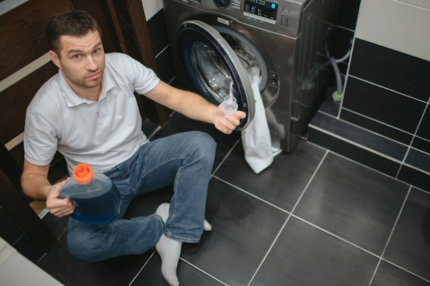 Poważny skoncentrowany facet w wannie trzyma płynny proszek i patrzy w kamerę.