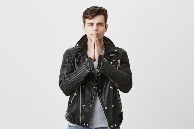 Poważny skoncentrowany mężczyzna w czarnej skórzanej kurtce trzyma dłonie razem, modli się o dobre samopoczucie rodziny, ma nadzieję na lepsze, ma silną wiarę. student martwi się o swoją przyszłość, prosi o szczęście