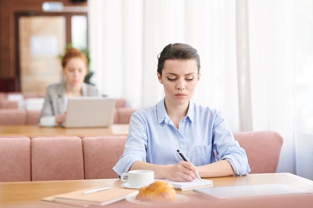 Poważny skoncentrowany młody bizneswoman w koszuli siedzi przy stole w nowoczesnej kawiarni i robienie notatek na biznesplanie