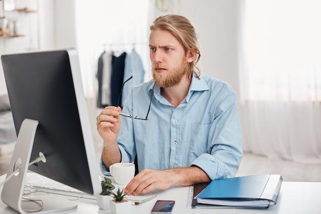 Poważny skoncentrowany zamyślony biznesmen w niebieskiej koszuli trzyma w ręku okulary, pracuje na komputerze, myśli o raporcie finansowym. brodaty manager lub freelancer pije kawę, generuje pomysły