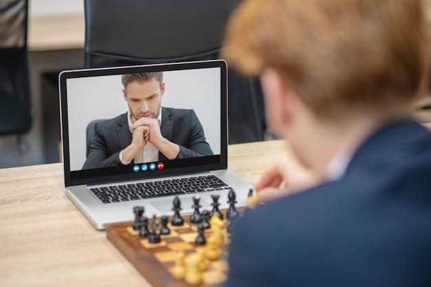 Poważny, skupiony mężczyzna w ciemnym garniturze, myślący o ruchu w szachy na ekranie laptopa i przeciwników z powrotem przy stole