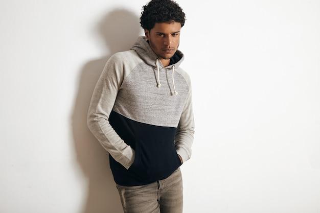 Poważny, smutny, czarny facet ma na sobie puste szare dżinsy i bluzę z kapturem, pozującą przed białą ścianą