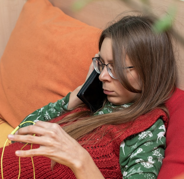 Poważny smutny zdenerwowany młoda kobieta ze smartfonem w dłoniach rozmawia przez telefon, siedząc na kanapie w domu. ludzkie emocje. selektywne skupienie. skopiuj miejsce na tekst.