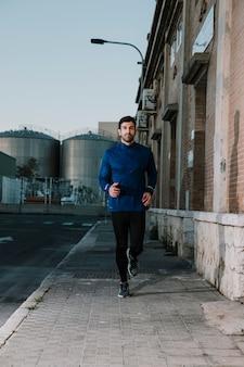 Poważny sportowiec działa na pustej ulicy