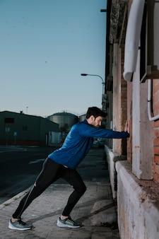 Poważny sportowiec opiera na ścianie i rozgrzewaniu