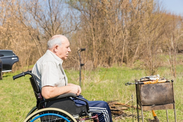 Poważny starszy mężczyzna siedzi na wózku inwalidzkim w parku, czekając na mięso z grilla do gotowania w upale słońca.
