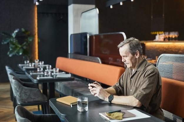 Poważny starszy mężczyzna w brązowej koszuli i zegarek siedzący przy stole i wysyłający sms-y na telefon podczas oczekiwania w kawiarni