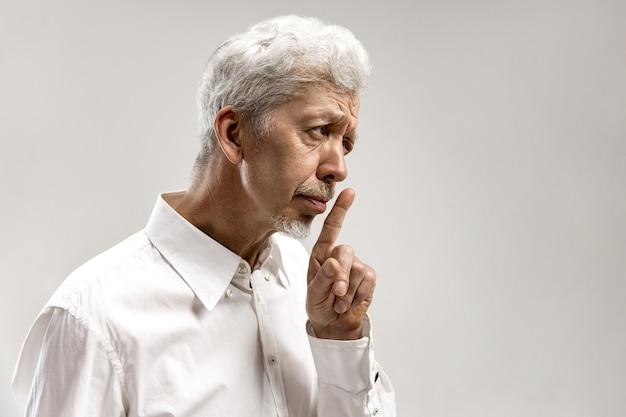 Poważny starszy przestraszony mężczyzna trzyma palec na ustach, stara się zachować spisek, mówi: ćśś, proszę zrób ciszę. na białym tle strzał człowieka pokazuje gest ciszy