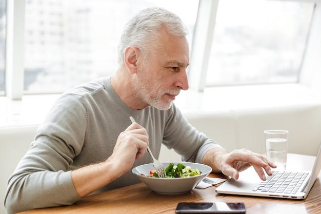 Poważny starszy siwy biznesmen brodaty starszy siedzieć w kawiarni zjeść obiad przy użyciu komputera przenośnego.