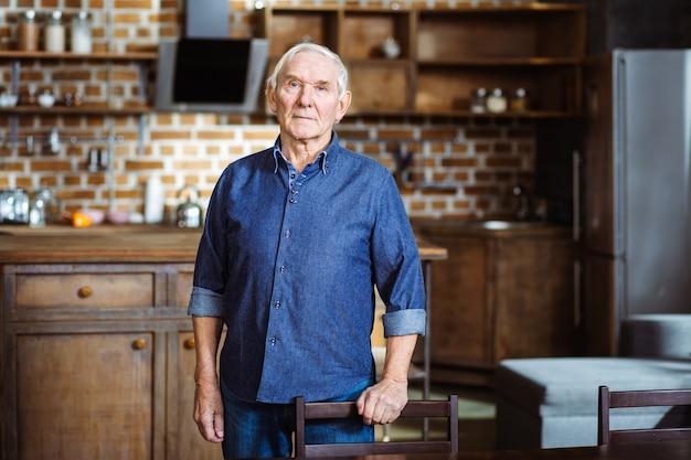 Poważny staruszek opierający się na krześle, stojąc w kuchni