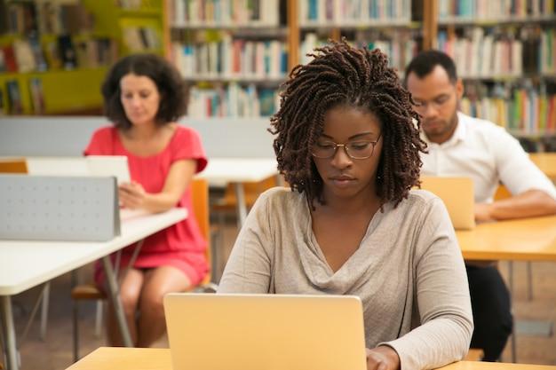 Poważny student african american studiuje w bibliotece