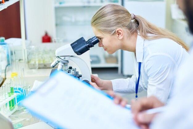 Poważny student medycyny analizuje próbkę przez mikroskopu
