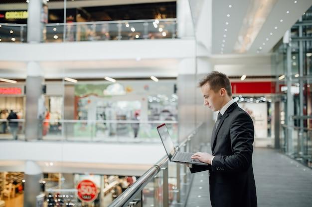 Poważny student na czacie w internecie z laptopem w ręku, ubrany w czarny garnitur, w centrum biznesowym, widok z boku