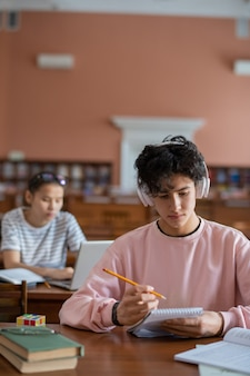 Poważny student w słuchawkach, słuchając muzyki podczas czytania notatek w notatniku
