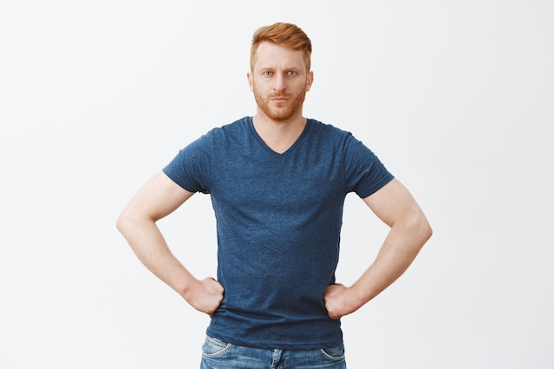 Poważny, surowy i przystojny rudy mężczyzna w niebieskiej koszulce, trzymający się za ręce w talii i wpatrujący się, besztający kogoś lub udzielający wskazówek, będąc apodyktycznym