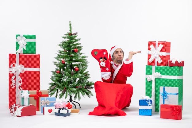 Poważny święty mikołaj siedzi na ziemi i nosi skarpety świąteczne w pobliżu prezentów i udekorowane drzewo noworoczne na białym tle