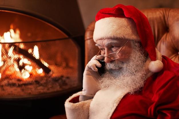 Poważny święty mikołaj w okularach siedzi przy kominku i rozmawia przez telefon komórkowy w ciemnym pokoju
