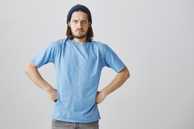 Poważny szalony hipster zbeształ kogoś, marszczy brwi i zdenerwowany