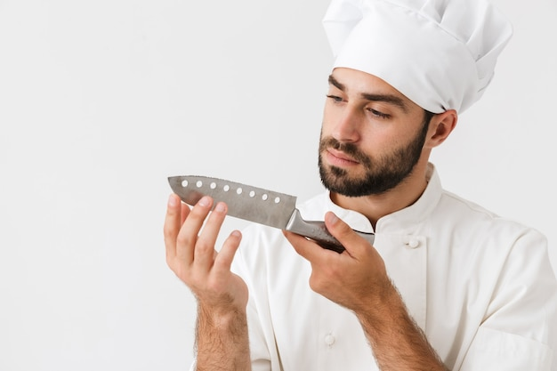 Poważny szef w mundurze kucharza, trzymający duży ostry metalowy nóż izolowany nad białą ścianą