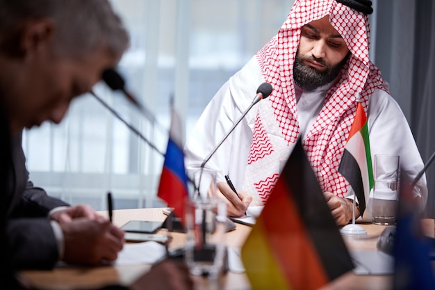 Poważny szejk w tradycyjnym stroju siedzi skoncentrowany, podpisując dokument na spotkaniu biznesowym w biurze