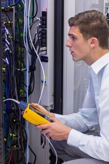 Poważny technik używa cyfrowego kablowego analyzer na serwerze