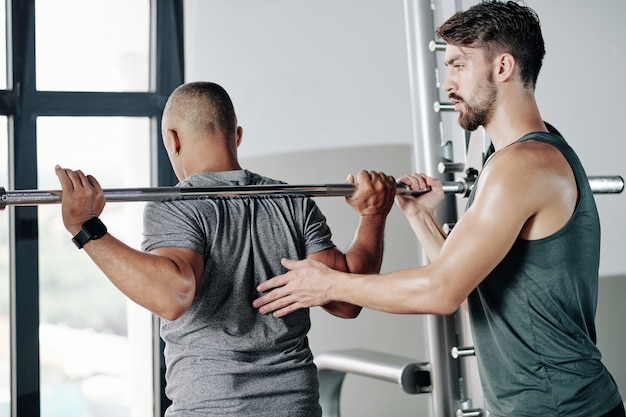 Poważny trener fitness kontrolujący klienta przygotowującego się do podniesienia ciężkiej sztangi