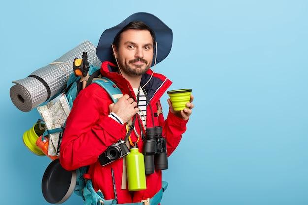 Poważny turysta mężczyzna nosi plecak z niezbędnym dla podróżnika sprzętem, lubi dalekie podróże, preferuje aktywny wypoczynek, pije kawę