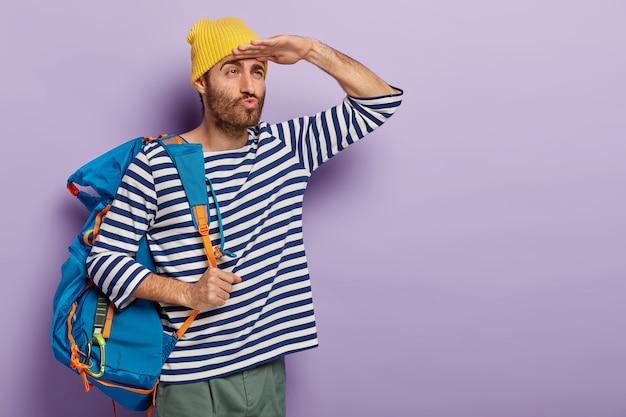Poważny turysta z plecakiem ma złożone usta