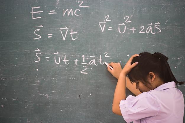 Poważny uczeń dziewczyna o formule fizyki w klasie.