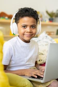 Poważny uczeń podstawówki afrykańskiego pochodzenia ze słuchawkami piszący na laptopie podczas słuchania w domu edukacyjnego kursu online