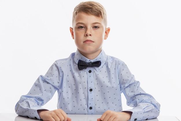 Poważny uczeń w niebieskiej koszuli z muszką siedzi przy stole.