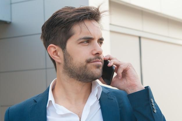 Poważny ufny biznesmen opowiada na telefonie komórkowym
