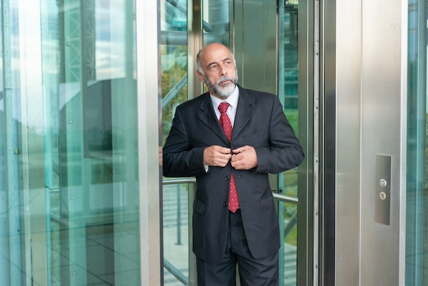 Poważny ufny dojrzały biznesmen używa biurową windę