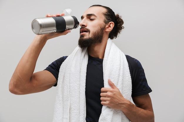 Poważny, umięśniony sportowiec z ręcznikiem na szyi, woda pitna po treningu na białym tle nad białą ścianą
