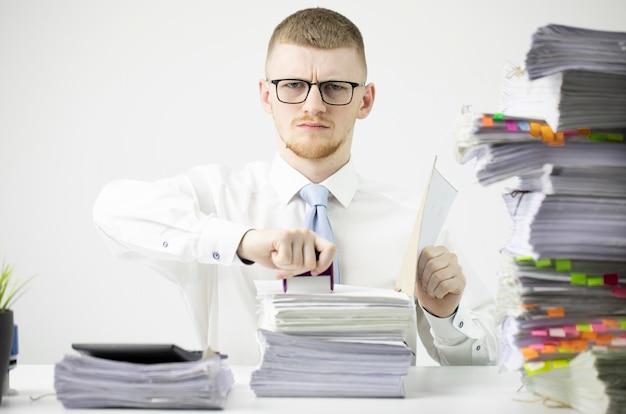 Poważny urzędnik w koszula z krawatem i szkłami siedzi przy stole z papierkową robotą