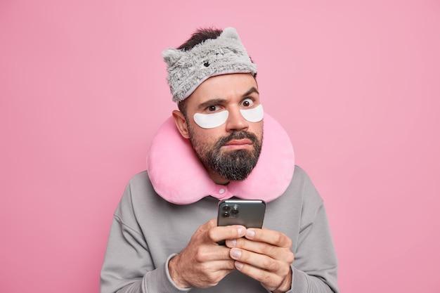 Poważny, uważny, zroszony dorosły mężczyzna nosi poduszkę podróżną sleepamsk na szyi, sprawdza smartfona