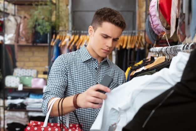 Poważny wybór. spokojny młody student marszczy brwi i patrzy na ubrania w sklepie