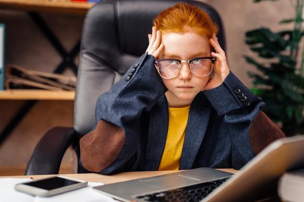 Poważny wygląd. poważna inteligentna dziewczyna dotykająca skroni, koncentrując się na swojej pracy