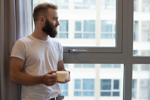 Poważny zadumany młody brodaty mężczyzna pije kawę