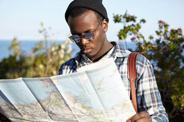 Poważny zagubiony czarny student europejski w stylowych ubraniach, stojący na tle błękitnego morza i zielonych drzew, zmartwiony spojrzeniem, próbujący znaleźć właściwą drogę na papierowym przewodniku