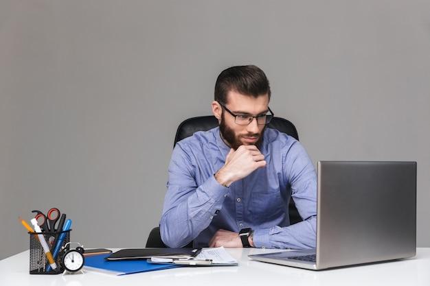 Poważny zamyślony brodaty elegancki mężczyzna w okularach trzymający się za brodę i korzystający z laptopa siedząc przy stole w biurze