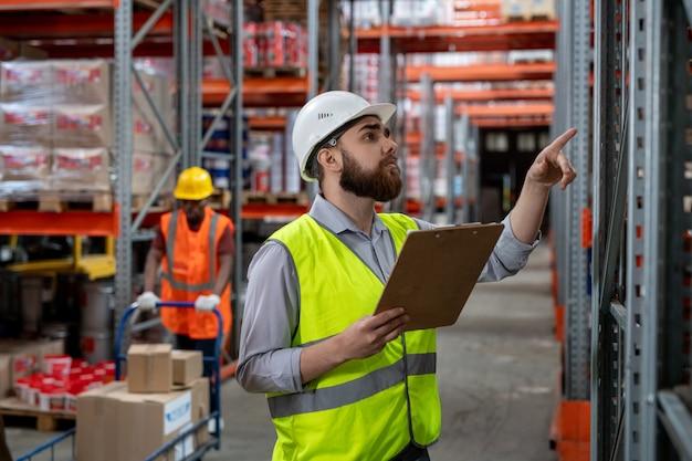 Poważny, zamyślony, brodaty kierownik magazynu w białym kasku i zielonej kamizelce trzymający schowek i liczący pudełka podczas kontroli towarów