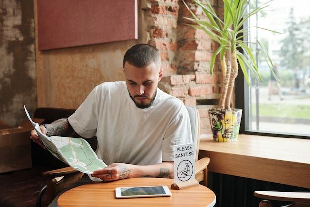 """Poważny, zamyślony, brodaty turysta siedzący przy małym stoliku z napisem """"proszę odkazić"""" w salonie i przeglądający papierową mapę"""