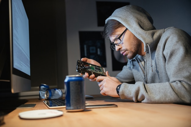 Poważny, zamyślony młody człowiek w okularach, myślący i patrzący na zepsuty dysk twardy w domu