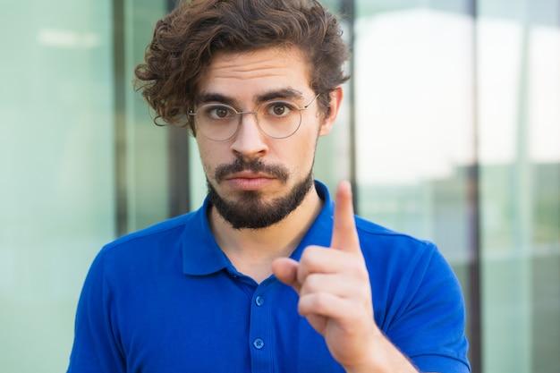 Poważny zaniepokojony facet wskazuje palec wskazujący w górę